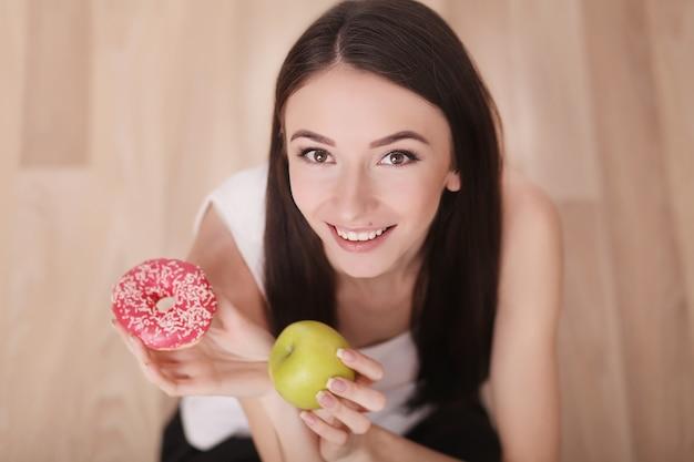 De slanke vrouw houdt in hand roze doughnut en groene appel