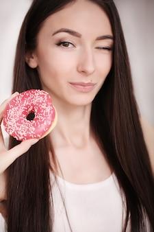 De slanke vrouw houdt in hand roze doughnut