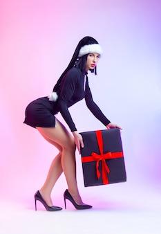 De slanke vrouw in een korte zwarte jurk met een kerstmanhoed en een groot cadeau in haar handen voor het nieuwe jaar