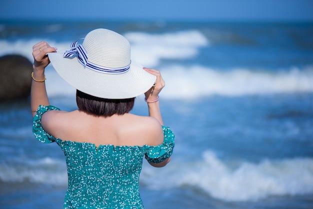 De slanke vrouw in moderne tinten gaat achteruit en de hoed