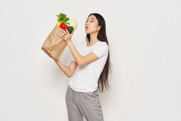 De slanke vrouw in sportkleding houdt in haar hand een pakket met groentencalorie