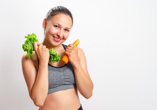 De slanke vrouw met een mooi cijfer houdt groenten in haar handen - wortelen en sla