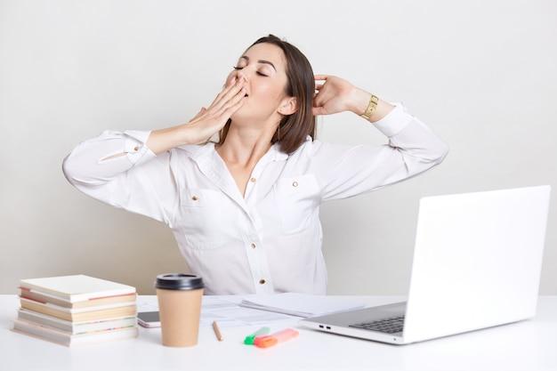De slaperige europese vrouw geeuwt en strekt zich uit, houdt hand op mond, draagt wit overhemd, gebruikt laptop computer, boeken, die over witte muur worden geïsoleerd. de onderneemster bereidt project voor, stelt binnen voor.