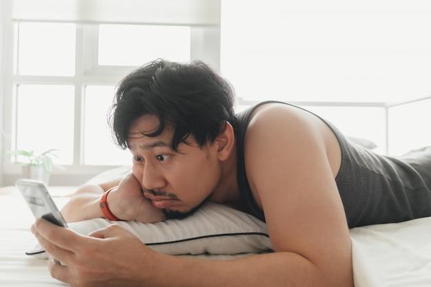 De slaperige mens gebruikt smartphone terwijl liggend op het bed.