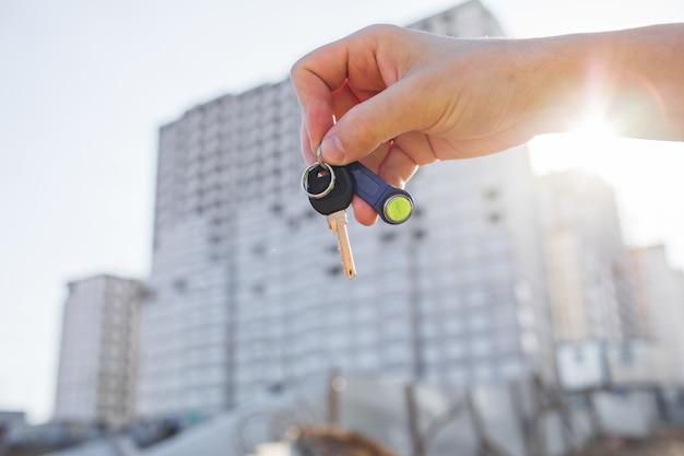 De sleutels van het appartement in de hand op de achtergrond van nieuwe woningen