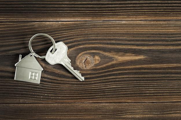 De sleutels van het huis liggen op het houten tafelblad. het uitzicht vanaf de top. het concept van het kopen van een nieuw huis.