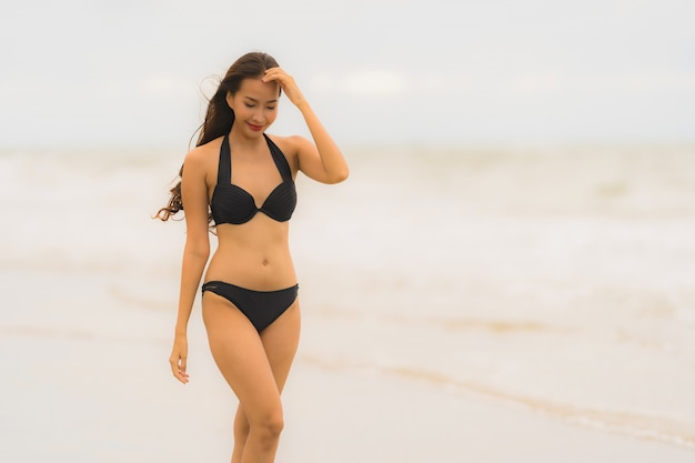 De slijtagebikini van de portret mooie jonge aziatische vrouw op de strand overzeese oceaan