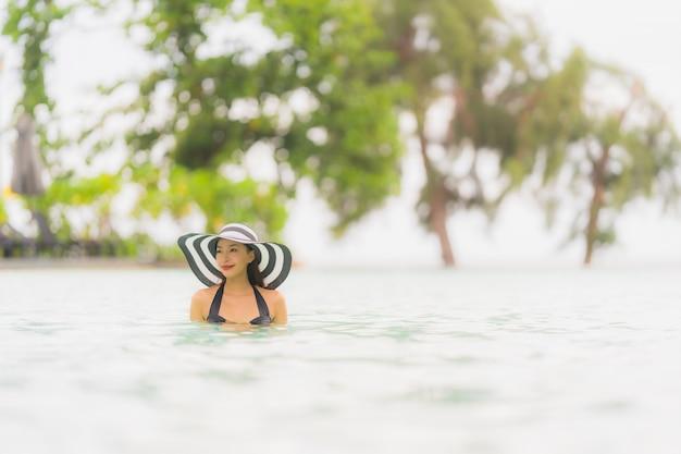 De slijtagebikini van de portret mooie jonge aziatische vrouw rond zwembad in hoteltoevlucht bijna overzees oceaanstrand