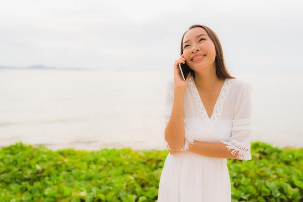 De slijtagehoed van de portret mooie aziatische vrouw met glimlach gelukkig voor sprekende mobiele telefoon op het strand