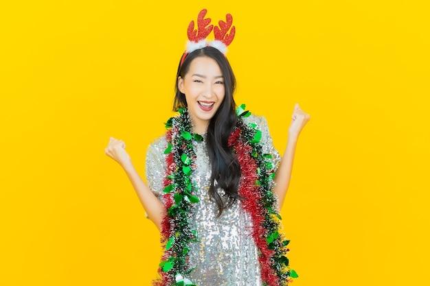 De slijtagekerstmisuitrusting van de portret mooie jonge aziatische vrouw op geel