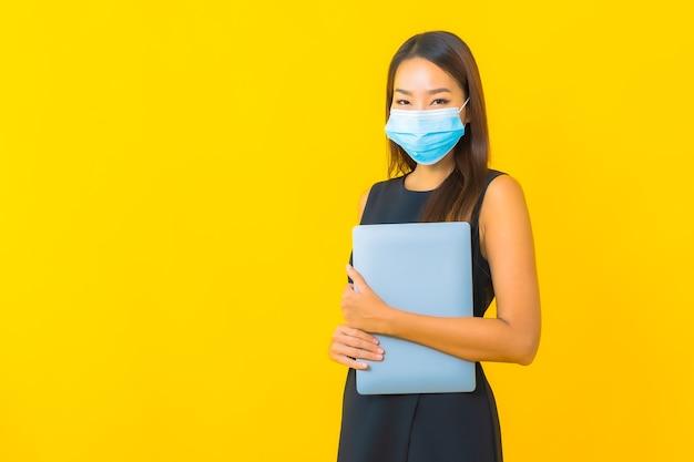 De slijtagemasker van het portret mooi jong aziatisch bedrijfsvrouw voor beschermt covid19 met laptop