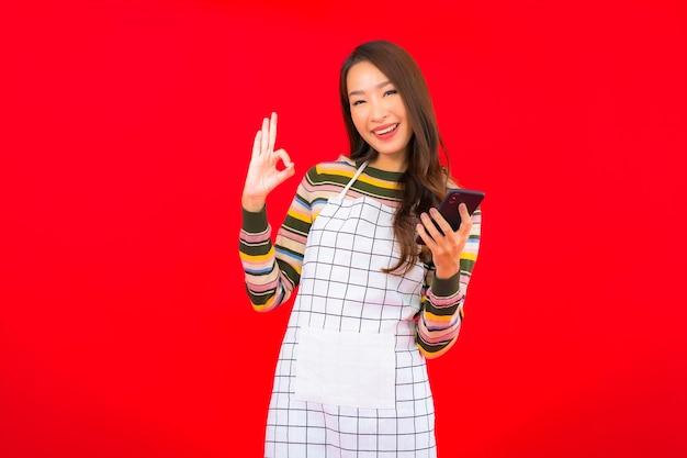 De slijtageschort van de portret mooie jonge aziatische vrouw met slimme mobiele telefoon op rode geïsoleerde muur