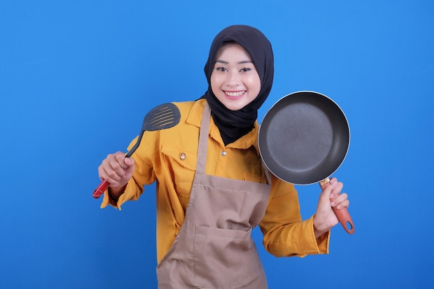 De slijtageschort van de portret mooie jonge aziatische vrouw met zwarte pan en spatel