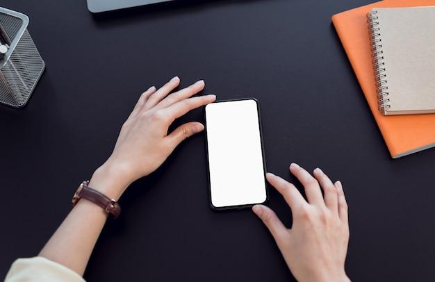 De slimme telefoon van de vrouwenhand met het lege exemplaar ruimtescherm.
