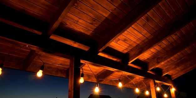 De slinger van gloeilampen die op het houten terras hangen
