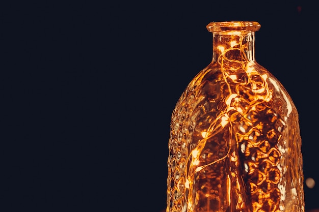 De slinger van kerstmislichten bracht fles in dark aan