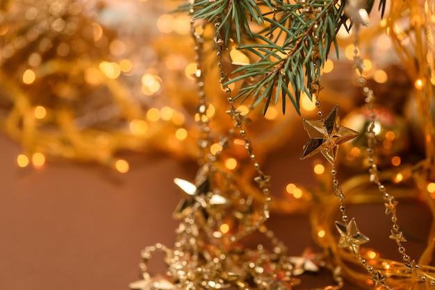 De slingerentakken van de kerstmissamenstelling op de achtergrond van kerstmisslinger