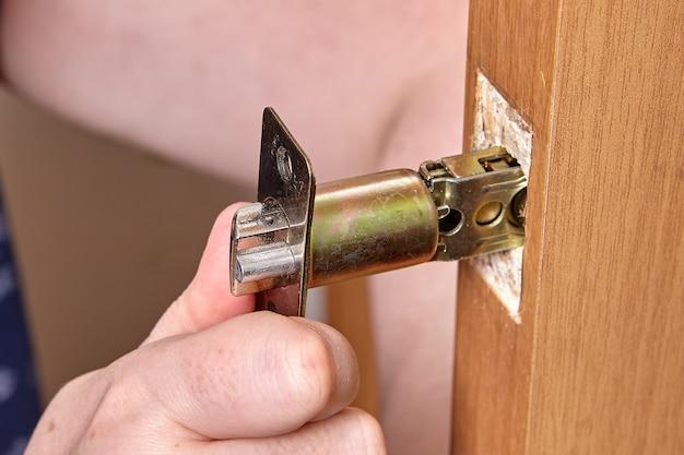 De slotenmaker steekt de grendel voor het deurklinkslot in het gat in het spaanplaatschild.