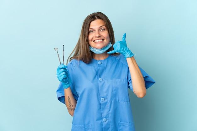 De slowaakse hulpmiddelen van de tandartsholding die op blauwe muur worden geïsoleerd die telefoongebaar maken. bel me terug teken