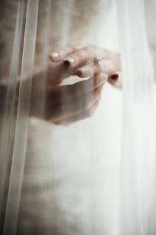 De sluier behandelt de handen van de bruid met trouwringen