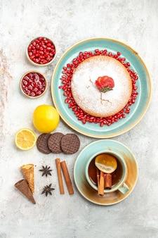 De smakelijke cake kaneelstokjes een kopje thee en de cake met aardbeien