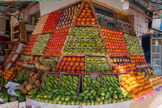 De smakelijke etalage van de fruitwinkel met veel dozen mango, sinaasappels, granaatappels, citroenen