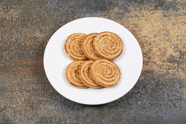 De smakelijke koekjes van sesamzaden op witte plaat.