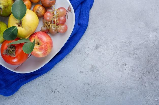 De smakelijke schotel van het fruitassortiment op blauw tafelkleed op marmeren achtergrond.