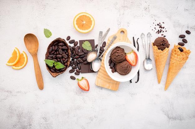 De smaken van het chocoladeroomijs in komopstelling op witte steen.