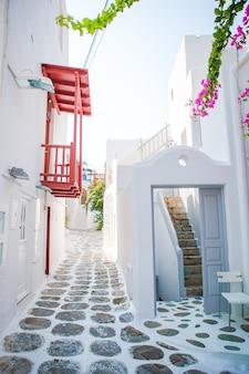 De smalle straatjes van het eiland met blauwe balkons, trappen en bloemen in griekenland.