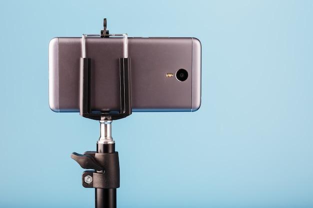 De smartphone is op een statief gemonteerd als foto-videocamera voor een blog op een blauwe achtergrond. neem video's en foto's op.