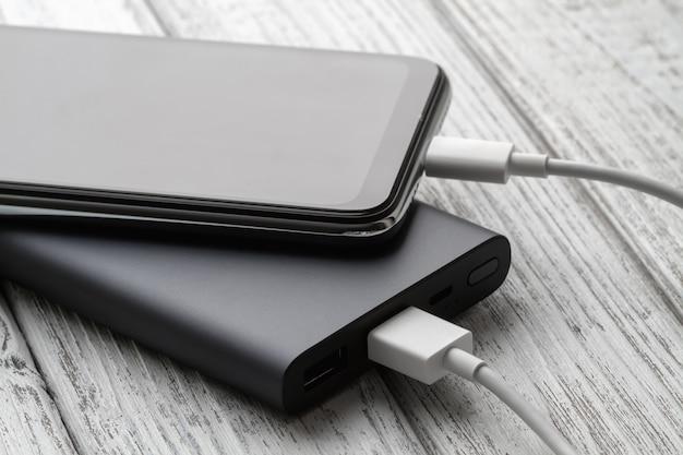 De smartphone laadt op van externe powerbank met kabel