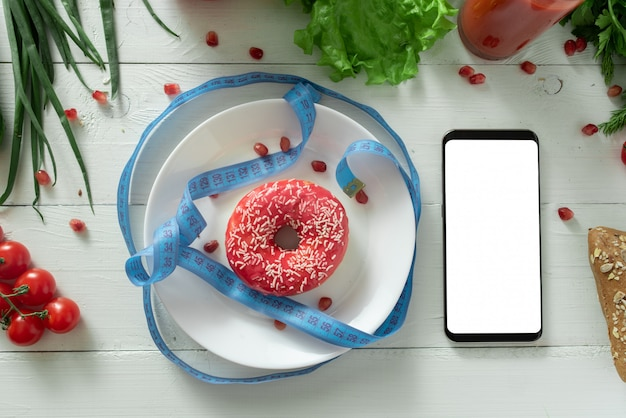 De smartphone ligt op een tafel met dieetgroenten. plaats voor uw tekst.