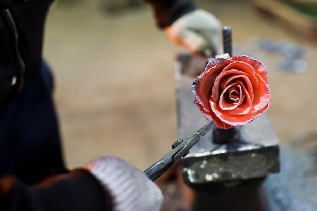 De smid smeedt stalen roos op het aambeeld