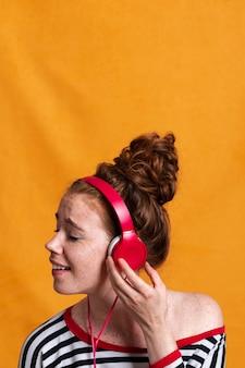 De smileyvrouw die van de close-up aan muziek met hoofdtelefoons luistert