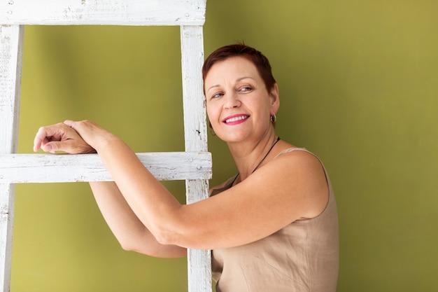 De smileyvrouw die van de close-up een ladder houdt