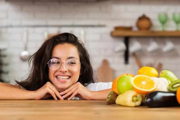 De smileyvrouw die van de close-up vruchten bekijkt