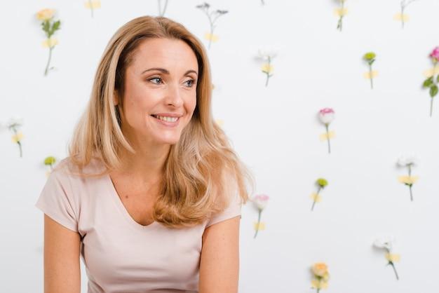 De smileyvrouw met de lente bloeit erachter muur