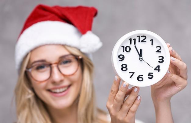 De smileyvrouw van de close-up met een klok