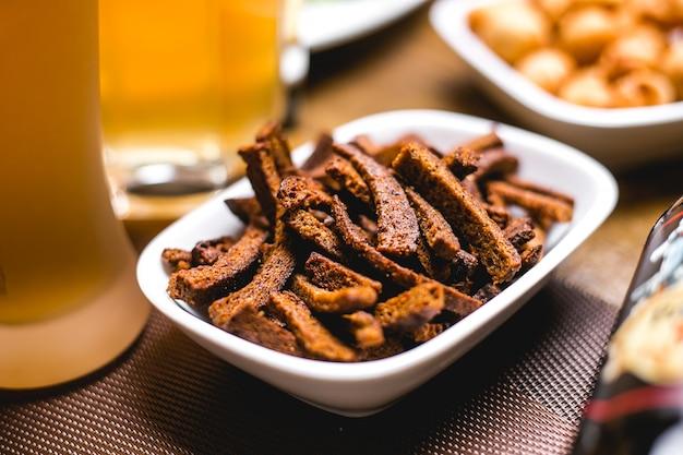 De snackcrackers van het zijaanzichtbier van bruin brood op een plaat worden gemaakt die