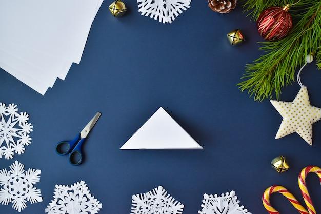 De sneeuwvlok is gemaakt van papier. stap 4 buig het vel en knip het overtollige af.
