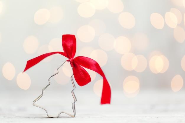 De snijder van het kerstboomkoekje met rode boog op witte achtergrond met exemplaarruimte. kerst concept.