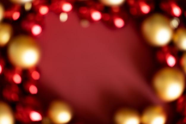 De snuisterijendecoratie van onduidelijk beeld rode kerstmis op rode achtergrond met exemplaarruimte. nieuwjaar wenskaart. minimale stijl. plat leggen.
