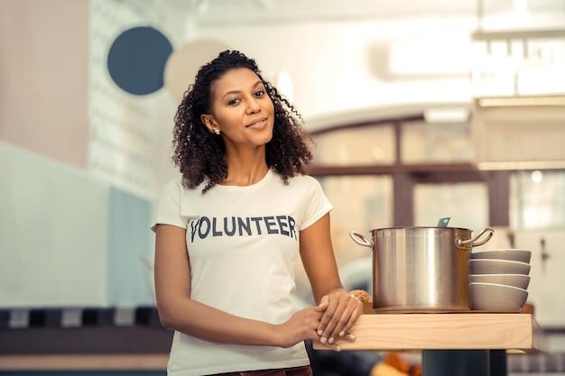 De soep is klaar. vrolijke afro-amerikaanse vrouw die lacht terwijl hij in de buurt van de pan staat