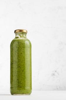 De soep van de broccoliroom in glasfles met lichte achtergrond en exemplaarruimte.