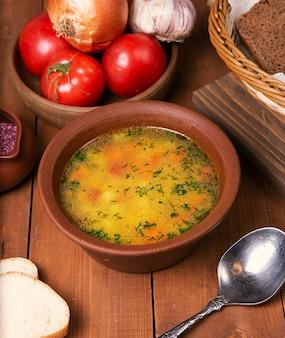 De soep van de kippenbouillon met gehakte peterselie in aardewerkkom.
