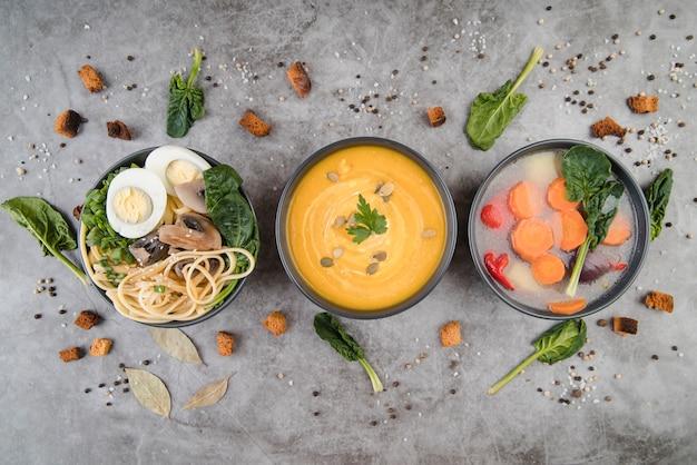 De soepen en de ingrediënten op vlakke keukentafel lagen