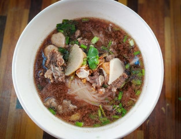 De soepkom van rundvleesnoedels met vleesbal en groente op houten lijstachtergrond