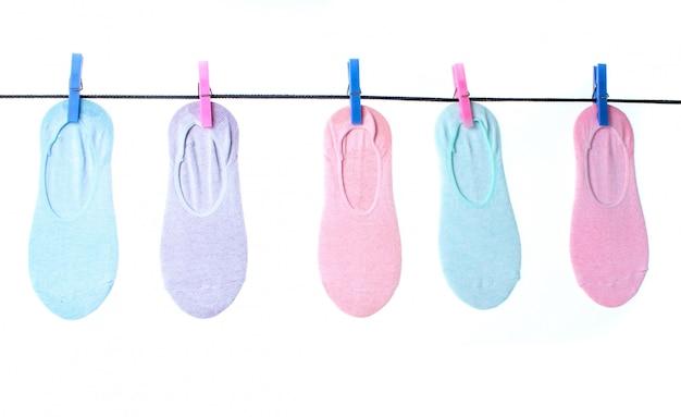 De sokken van vrouwen hangen op geïsoleerde wasknijperwaslijn