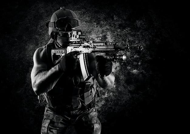 De soldaat van de speciale eenheid mikt op de collimatorvizier van zijn machinegeweer. gemengde media